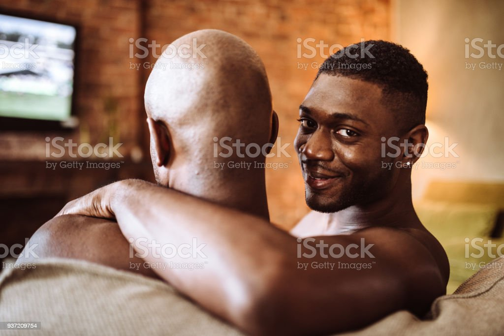 gay couple watching the tv on the sofa stock photo