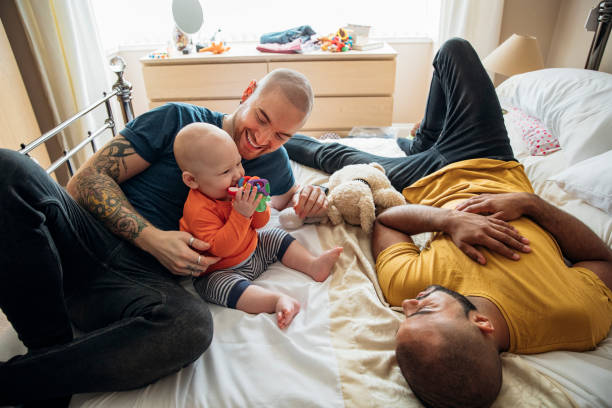 Gay Couple Watching Their Son Play Gay fathers lying on their bed with their son watching him play with his toys. gay person stock pictures, royalty-free photos & images