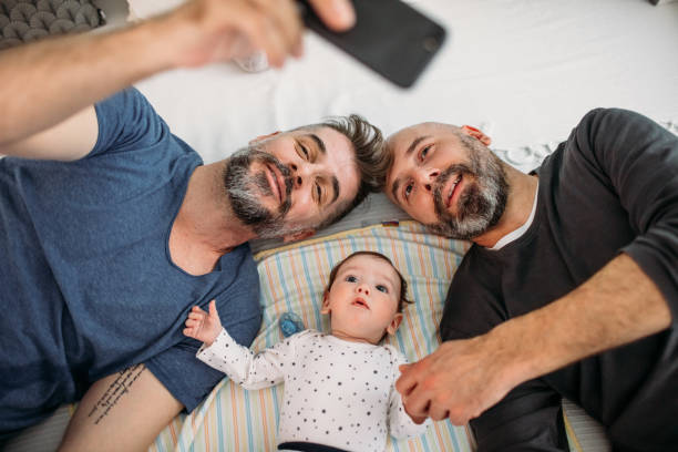 Gay Dads Gay dads playing with their adopted baby in the bedroom. gay person stock pictures, royalty-free photos & images