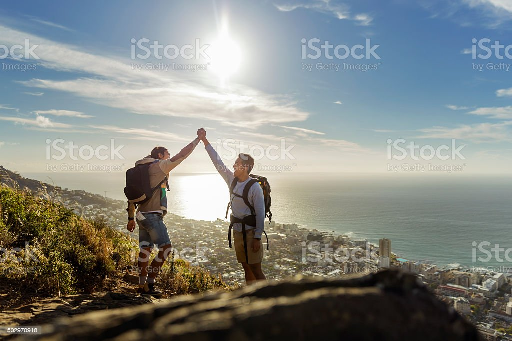Gay hikers celebrating success on hill stock photo