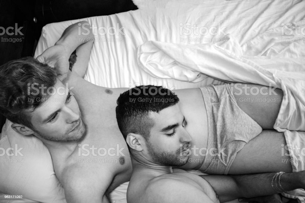 Gay lovers, husbands in bed holding each other stock photo