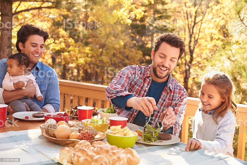 Gay Male Couple Having Outdoor Lunch With Daughters stock photo