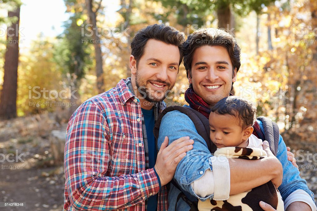 Gay Male Couple With Baby Walking Through Fall Woodland stock photo