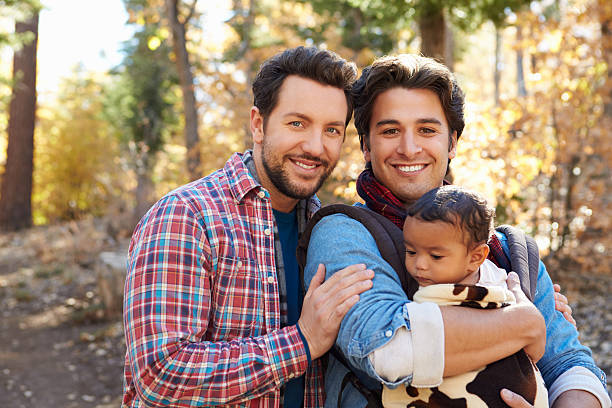 Gay Male Couple With Baby Walking Through Fall Woodland Gay Male Couple With Baby Walking Through Fall Woodland gay person stock pictures, royalty-free photos & images