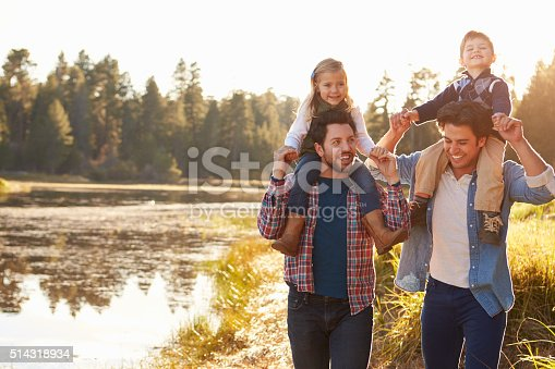 istock Gay Male Couple With Children Walking By Lake 514318934