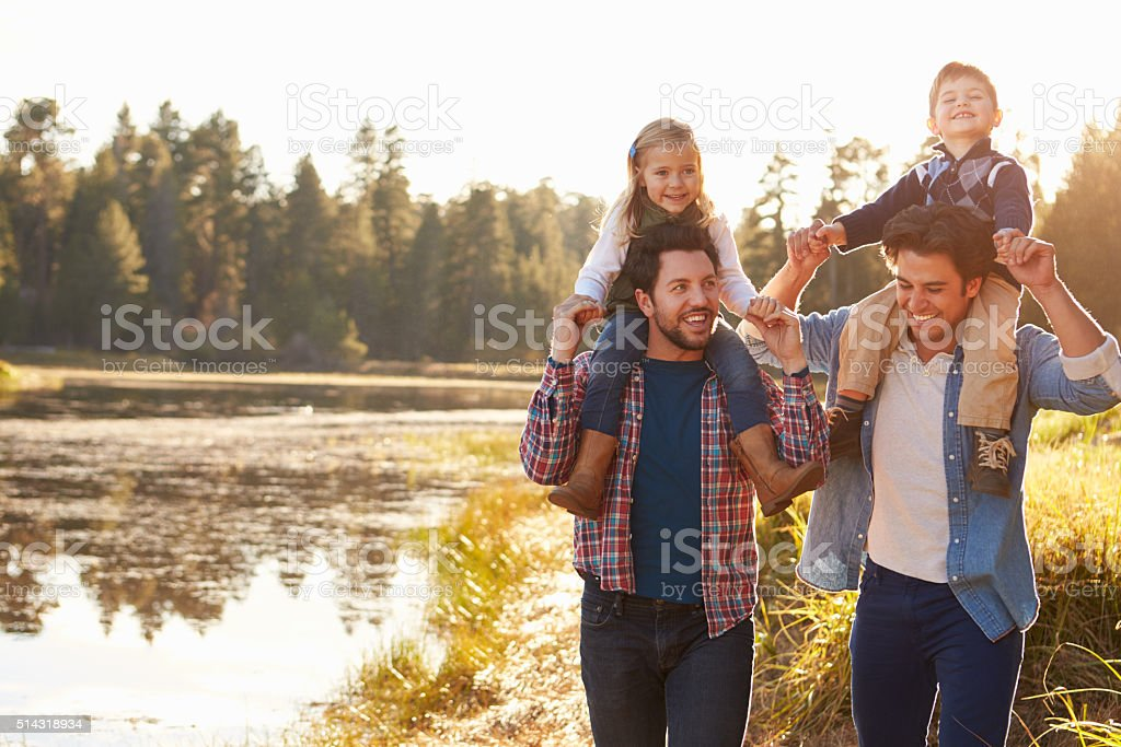Gay Male Couple With Children Walking By Lake stock photo