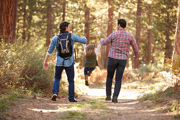 Gay Male Couple With Daughter Walking Through Fall Woodland Gay Male Couple With Daughter Walking Through Fall Woodland gay person stock pictures, royalty-free photos & images