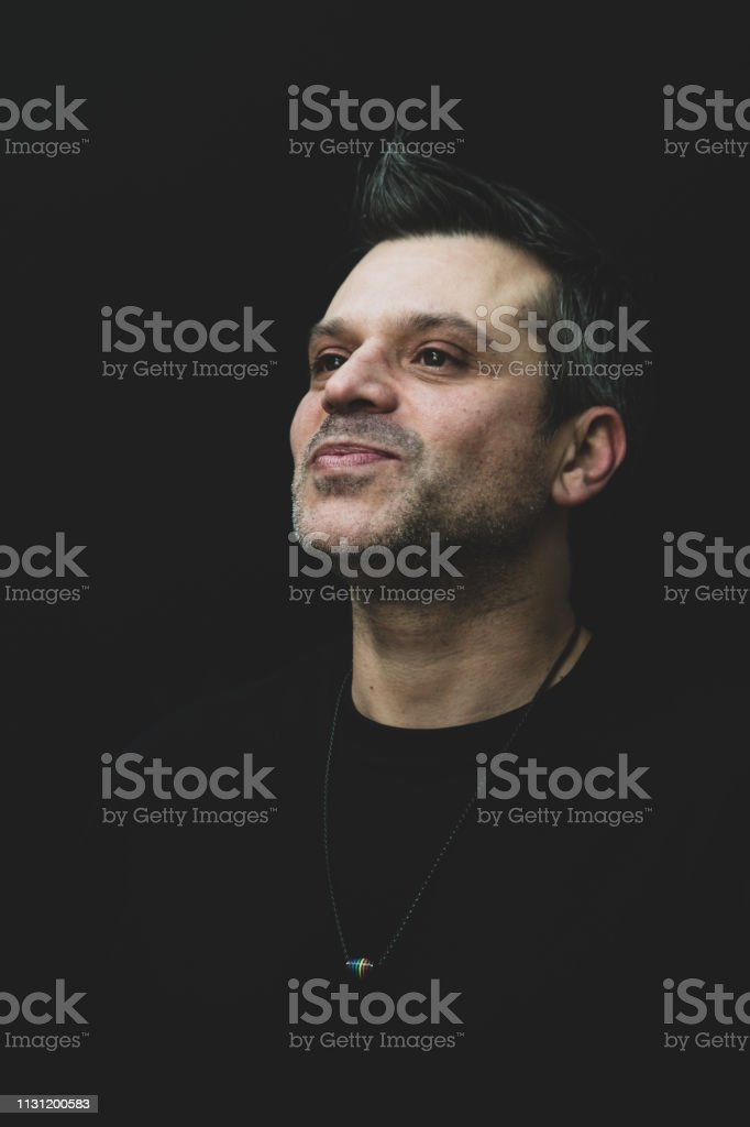 A gay man with stubble and short hair - poses wearing a pride...