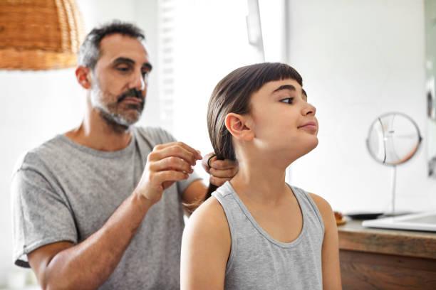 gay man is tying daughter's hair in bathroom - covid hair imagens e fotografias de stock
