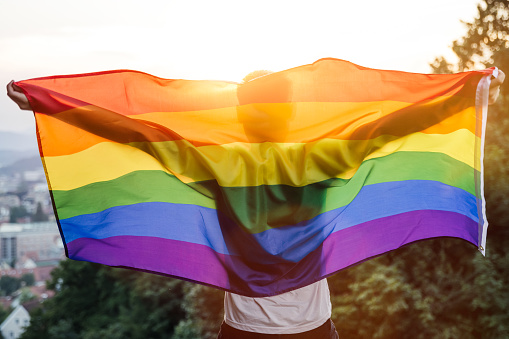 Gay man stanting with LGBT flag on sunset