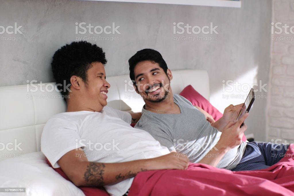 Gay Man Playing Video With Partner In Bed stock photo