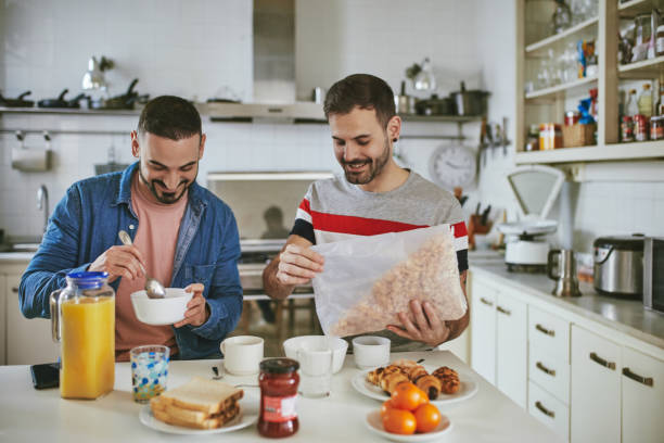 Gay man pouring cereals in bowl by partner at home stock photo