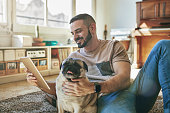 Smiling gay man using digital tablet while relaxing by pug on carpet. Mid adult man is spending leisure time with pet in living room. He is in casual at home.