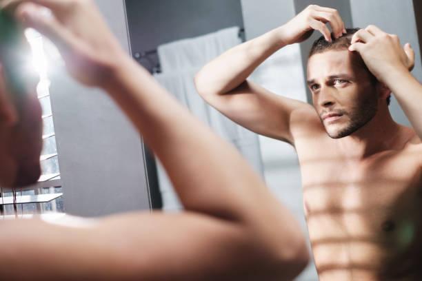 Gay Man sorgt sich um Haarausfall Alopecia im heimischen Badezimmer – Foto