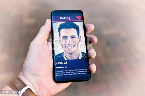 505935220istockphoto Gay man's hand holds a phone displaying another man on an internet dating site 1182274564