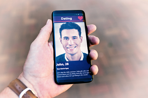 505935220 istock photo Gay man's hand holds a phone displaying another man on an internet dating site 1182274564
