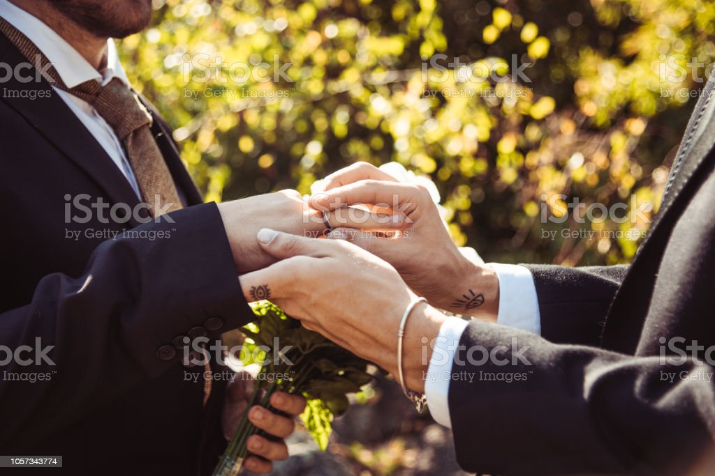 gay marriage, man putting the ring stock photo