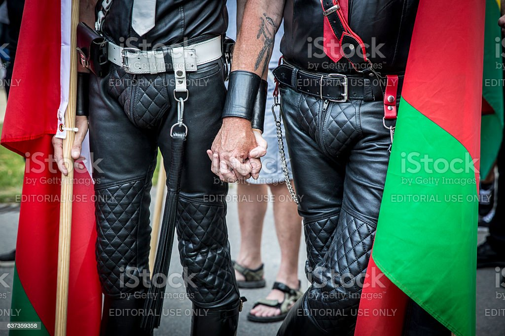 2 gay men wearing leather pants holding hands stock photo
