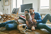 Gay men with daughter using digital tablet in living room. Family with pug spending weekend together. They are at home.