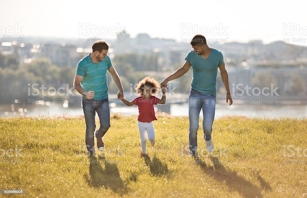 Gay parents running in the park with their adopted daughter. stock photo