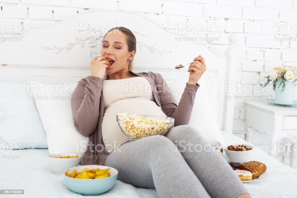 Gay pregnant woman biting bun royalty-free stock photo