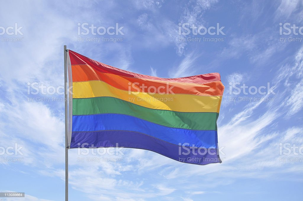 Gay Pride Flag Pole Waving in Blue Cloudscape Sky stock photo