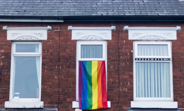 Gay pride LGBTQ flag flying from a house window stock photo