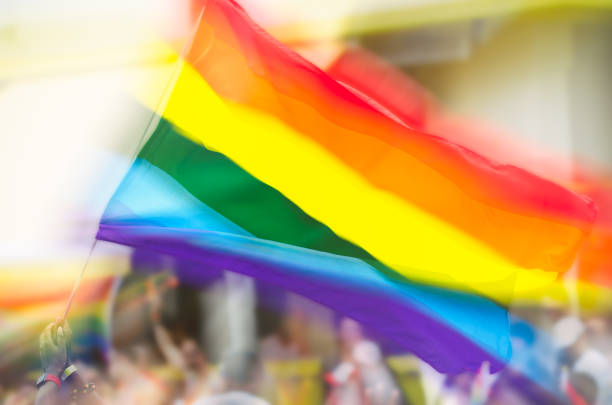 Gay Pride Rainbow Flag Flying in Crowd stock photo