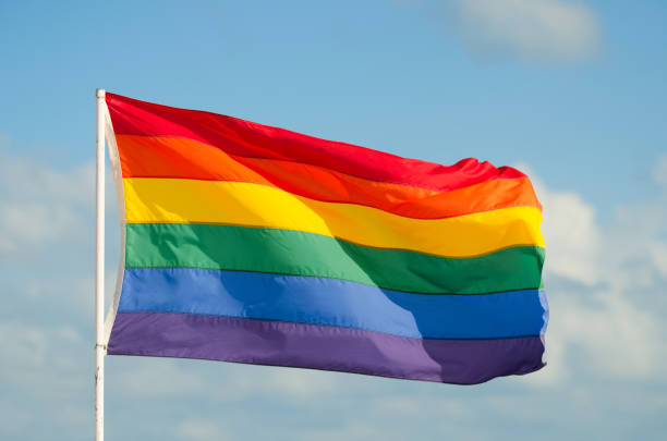 Gay Pride Rainbow Flag Flying in the Wind on Flag Pole stock photo