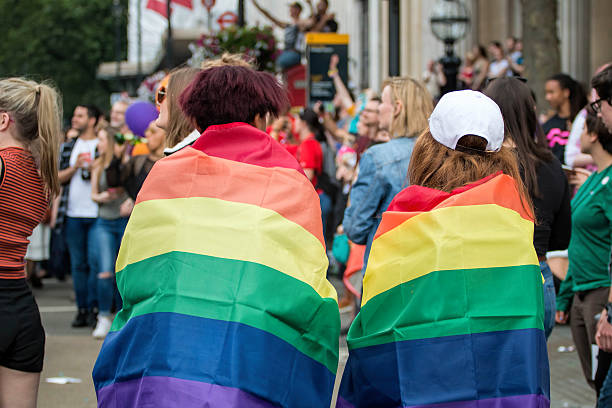 LGBT Gay Pride Two Young Woman Wrapped In Rainbow Flags stock photo
