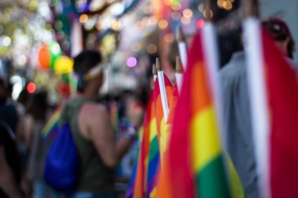 背景にぼやけた参加者とゲイプライドパレードでゲイ虹の旗 - lgbtqi  ストックフォトと画像