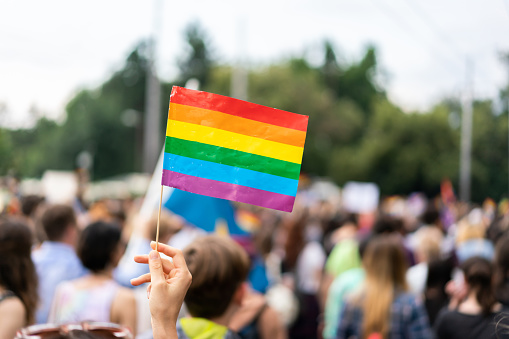 Gay Rainbow Flag At Gay Pride Parade With Blurred Participants In The Background Stock Photo - Download Image Now