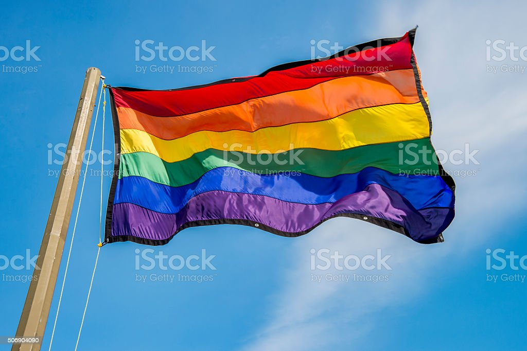 Gay rainbow flags waving over blue sky background stock photo