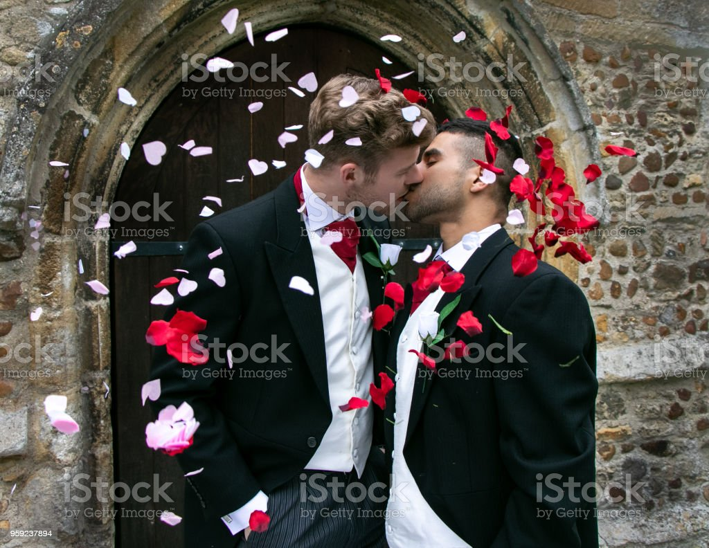 Gay wedding, grooms leave village church after being married to smiles and confetti stock photo