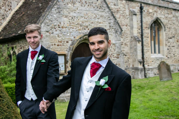 Gay wedding, grooms leave village church after being married with big smiles and holding hands stock photo