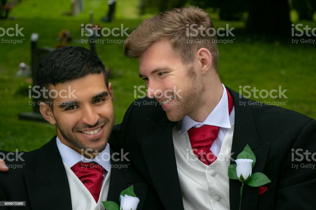 Gay weddings, grooms, couples pose for pictures after their wedding ceremony in churchyard stock photo