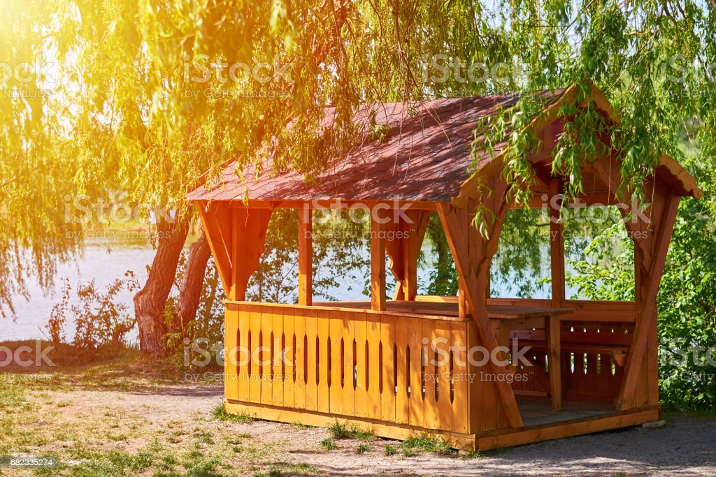 gazebo for family entertainment and is made of wood, stands on the shore of the lake foto de stock libre de derechos
