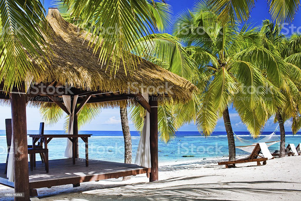 Gazebo with chairs on deserted beach and palm trees stock photo