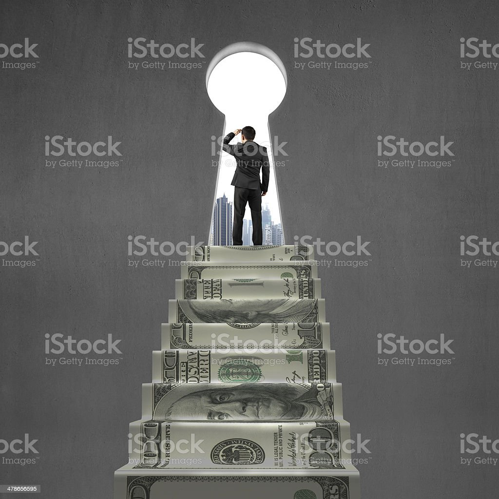 Gazing on top of money stairs with key hole stock photo
