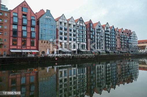 istock Gdansk - A panoramic view on the shores of Martwa Wisla flowing through Gdansk in Poland. The buildings reflect in the calm surface 1318687649