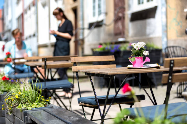Gdansk, Poland, 2017 05 22: tables and chairs on the street - waitress and client in the background stock photo