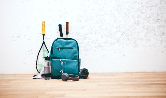 Shot of a sports bag and other items in an empty squash court
