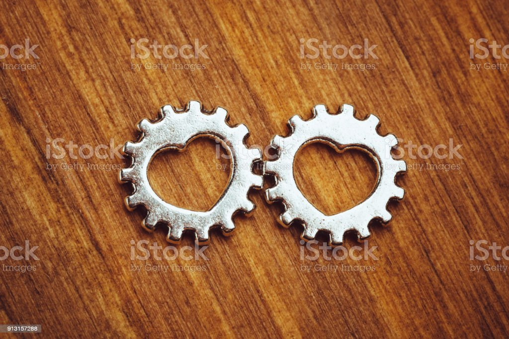 gear wheels with heart symbol, wooden background stock photo