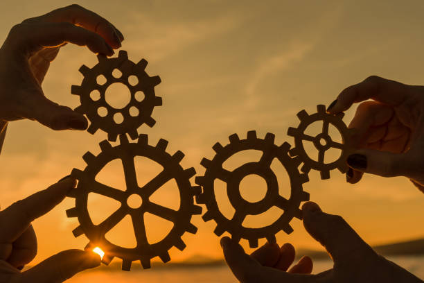 gears in the hands of a team of people against the sunset, teamwork stock photo
