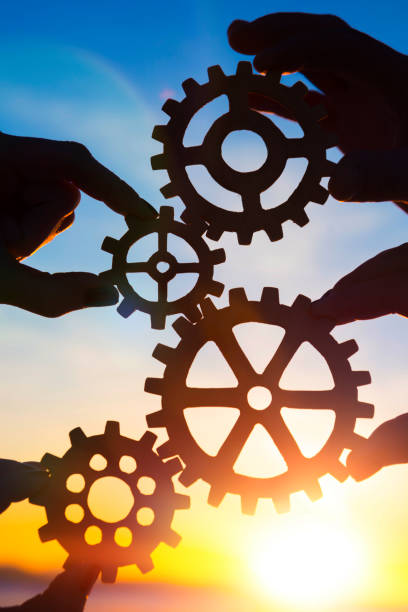 gears in the hands of people against the sky. stock photo