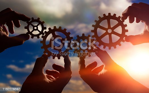 gears in the hands of people against the sky. mechanism, work in the company