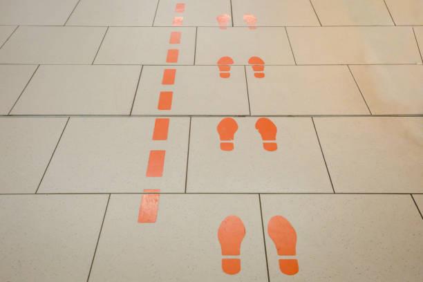 Zahnräder mit orangefarbenen Füßen auf dem Boden – Foto