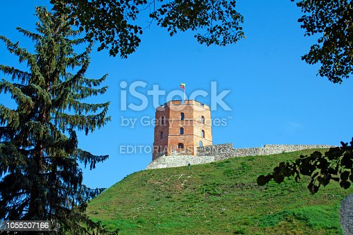 Vilnius / Lithuania - September 2 2018: Gediminas' Tower or Castle, the remaining part of the Upper Castle in Vilnius, Lithuania with lithuanian flag waving on a green hill and blue sky