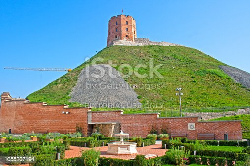 Vilnius / Lithuania - September 2 2018: Gediminas' Tower or Castle, the remaining part of the Upper Castle in Vilnius, Lithuania with lithuanian flag waving on a green hill and blue sky photographed from a garden with fountain