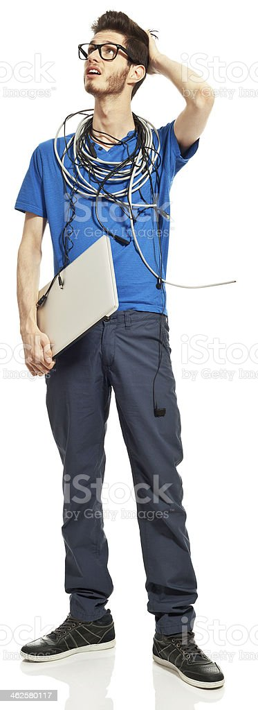 Geek Portrait of distraught young man with a lot of cables on his neck, holding a laptop in hand, looking up with hand in hear. Studio shot, white background. 18-19 Years Stock Photo